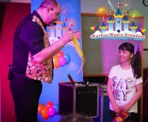 children's entertainer Lincoln - magician performing with the help of an assistant from the audience.